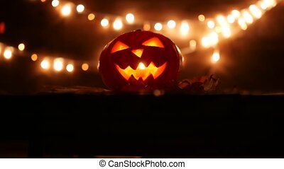Carved Halloween pumpkin with lights on background. Dark key...