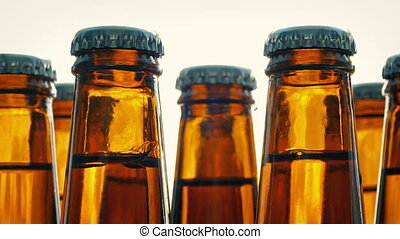 Beer Bottles Rotating On Plain Background - Closeup of...
