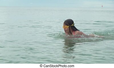 Young girl in sports glasses is floating in sea stock...