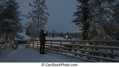 Man making photos on winter resort in the evening - Man...