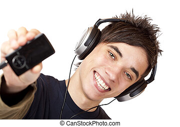 Happy male Teenager with headphones shows mp3 music player...