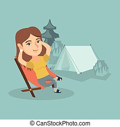 Woman sitting in a folding chair in the camping. - Young...