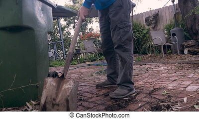 Hand held of an older senior using a shovel to clean up his...