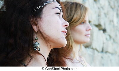 two women profile near the stone wall in shade