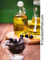 olive and oil - olives and olive oil in bottle, on a wooden...