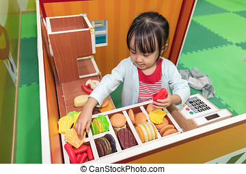 Asian Chinese little girl role-playing at burger store at...