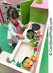 Asian Chinese little girl role-playing at kitchen at indoor...