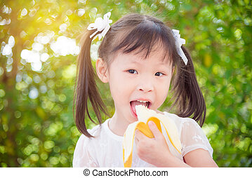 girl eating banana and smiles between picnic in park -...