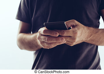 Modern new smartphone in hands of young casual man