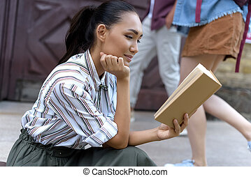 student reading book - happy attractive female asian student...