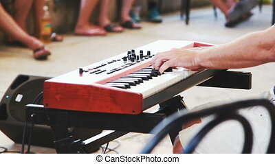 man hands play on the music synthesizer on party