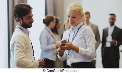 couple with smartphone at business conference - business,...