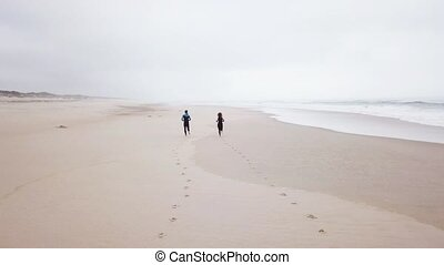 Young couple of friendly surfers running before entering the...