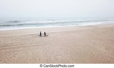 Young couple of friendly surfers wearing wetsuit, preparing...