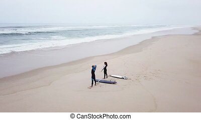 Young couple of friendly surfers exercising before entering...