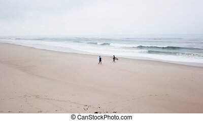 Young couple of friendly surfers wearing wetsuit holding...