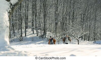 Teenagers on a walk in winter nature.Two boys having a race...