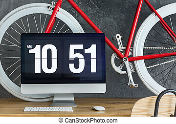 Red bicycle on wooden desk - Close-up of computer monitor,...