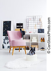 Black hat on pink chair in bright closet with shoes and...