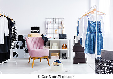 Pink chair in bright dressing-room with clothes shoes and...