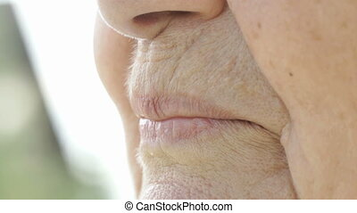 Smiling mouth of old woman with false teeth. Close up