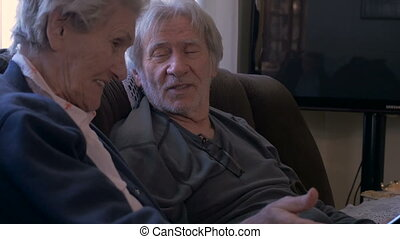 Two elderly people laughing, talking, and looking at a...