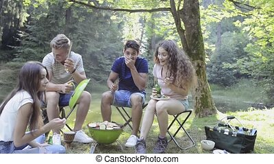 Teenagers camping, cooking meat on barbecue grill. -...