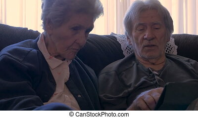 An elderly man explains to an older woman details about...