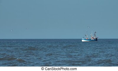 Fishing trawler boat in sea at the distance
