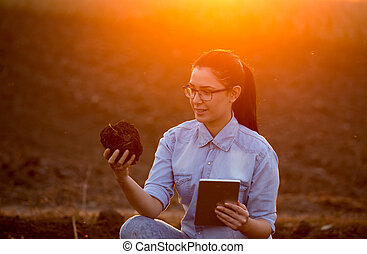Woman with tablet and earth clod - Pretty young engineer...