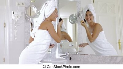 Laughing woman doing makeup in bathroom - Side view of young...