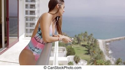 Young girl with gadget on hotel balcony - Side view of young...