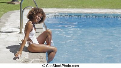 Attractive woman sitting on poolside - Side view of pretty...