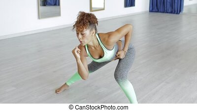 Woman bending in dance class - Attractive young black woman...