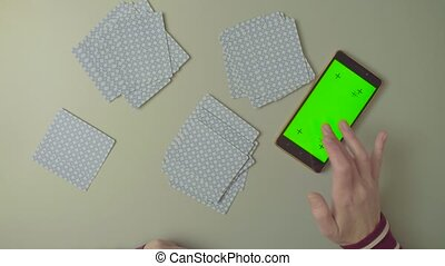 Green screen. Female hands with playing cards - Top view....
