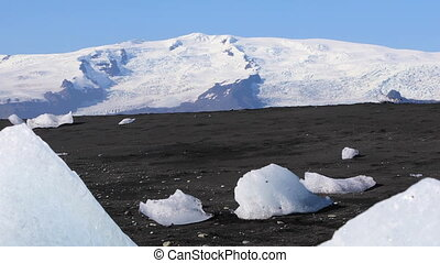 Woman hiking on black sand iceberg beach - Woman wearing...