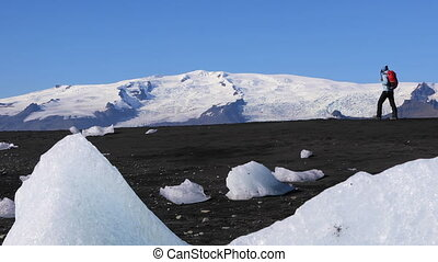 Young woman walking on black sand iceberg beach - Young...