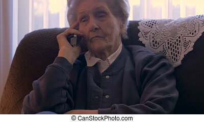 Blind elderly woman in her home listens on a phone looking...