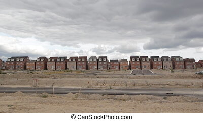 New houses. Car drives by. - Recently built homes at a new...