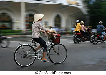 Vietnam Woman Cycling - Woman cycling on busy Hanoi Roadwith...