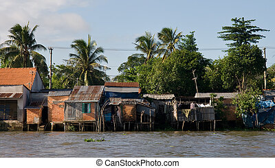 Mekong river huts - Huts line waters edge on the Mekong...