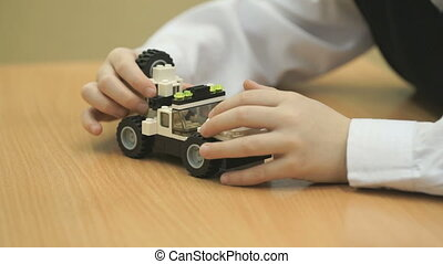Boy's hands collect a car from designer - Close-up of...