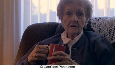 A senior women tells a story while drinking a cup of coffee...
