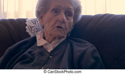 An elderly woman talking and using her hands to make point while sitting on sofa