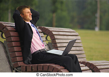 Young businessman is sitting at the park and using laptop