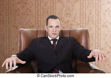 Businessman upset seated on a chair,
