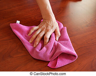 Wiping rag - hand wiping wooden surface with pink rag