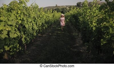 Happy girl running between the rows of vines and whirls