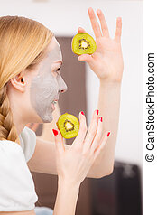 Happy young woman having face mask holding kiwi - Facial dry...