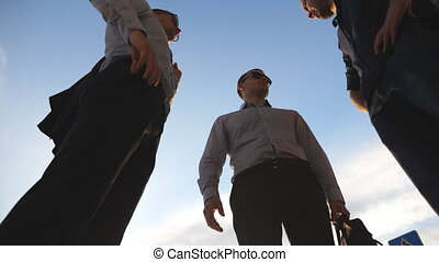 Low angle view of three business men standing outdoor and...